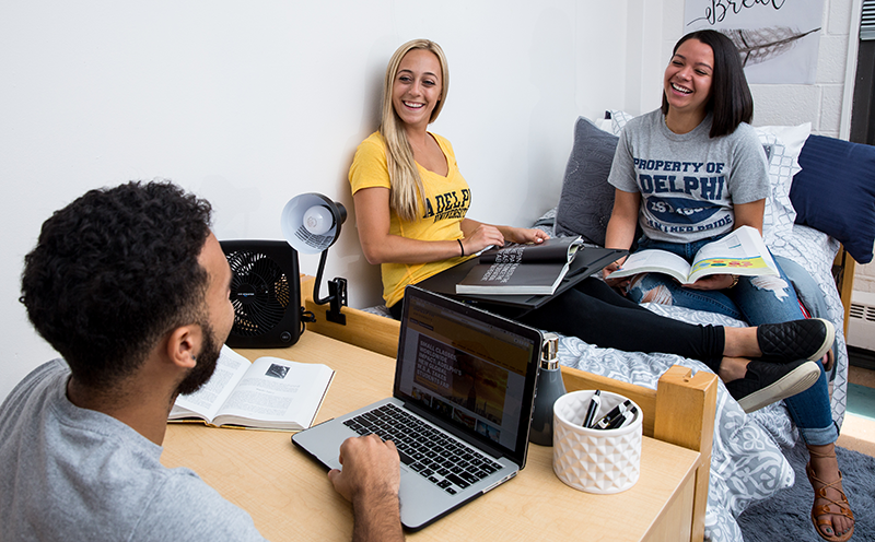 Adelphi students talking and studying in a dorm room